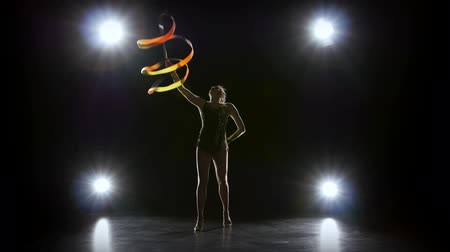 fitas : Gymnast with the ribbon in his hands doing acrobatic moves. Black background. Light rear