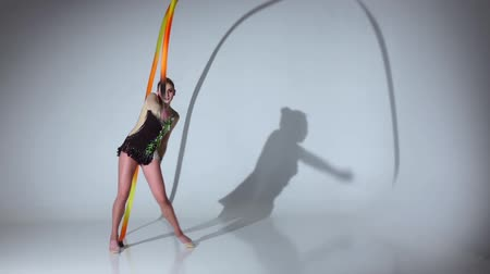 gymnasta : Rhythmic gymnast doing acrobatic moves with the tape. White background. Slow motion