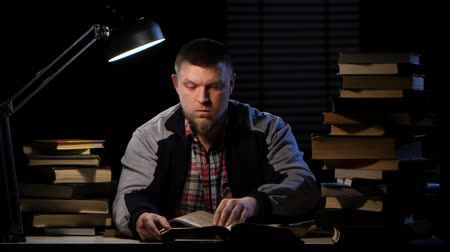 terribly : Guy looking for the right information in the book and could not find it. Black background Stock Footage