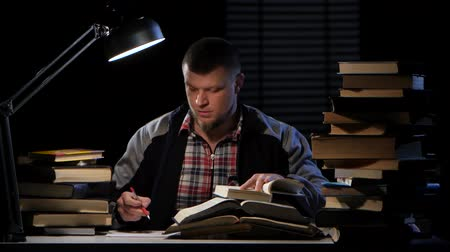 terribly : Guy looking for the right information in the book and could not find it. Black background. Time lapse Stock Footage