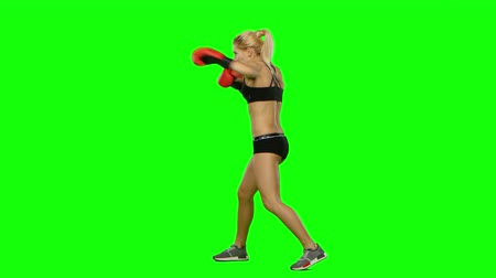 bajnok : Girl kickboxer in a special form of training for competitions. Green screen. Side view