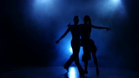 дымный : Silhouette of pair dancers performing modern dance in smoky studio