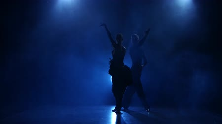 latino americana : Silhouette of pair dancers performing samba dance in smoky studio