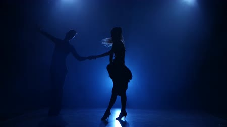 дымный : Silhouette of pair dancers performing latino dance in smoky studio