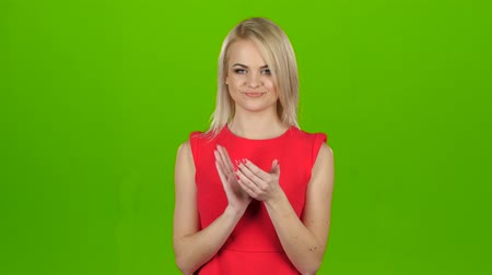 médio : Girl reluctant applauds with her both hands. Green screen studio