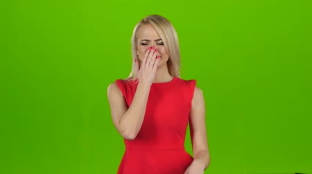 жест : Blonde yawns covering her mouth with hand. Green screen studio