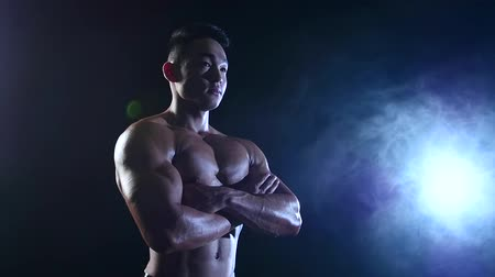 atlet : Asian bodybuilder demonstrates his body, strength and endurance. Black smoke background. Slow motion