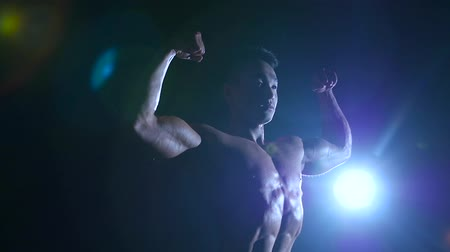 fisiculturismo : Asian muscular man shows demonstrates muscles. Black background. Slow motion . Silhouette Stock Footage