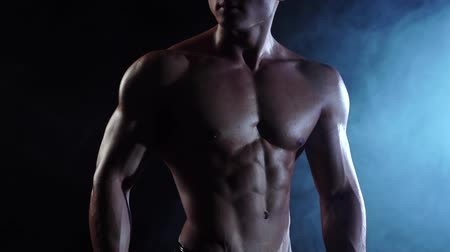 сильный : Weightlifter demonstrates his body, strength and endurance. Black smoke background. Slow motion. Close up