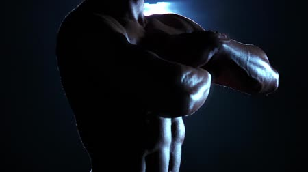 atleta : Bodybuilder demonstrates his body, strength and endurance. Black background. Slow motion Stock Footage