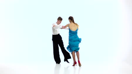 латинский : Pair of professional dancers perform salsa, white background. Slow motion