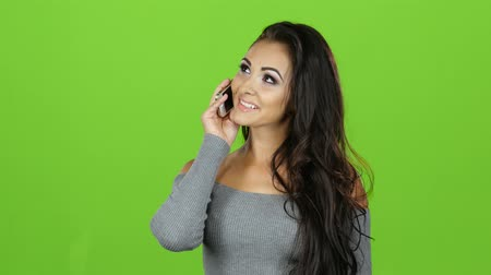 черные волосы : Brunette with smile talking on mobile phone, green screen background