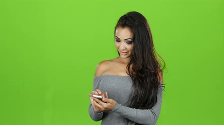 chroma key background : Brunette woman with smile plays on mobile, green screen background