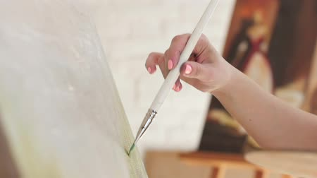 initial : Artist brush does strokes oil paint on canvas, slow motion Stock Footage