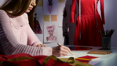 alkotás : Designer draws a sketch in the background is a mannequin with a red dress. Close up