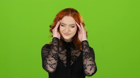 redhead suit : Girl has a headache, pressure pulsates in the temples. Green screen