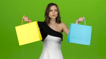 queda : Girl keeps the shopping bags and doubts what to choose. Green screen