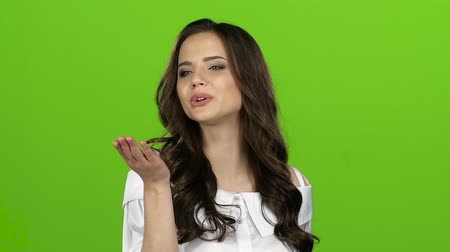 titkár : Brunette of sends kisses to others, waves her hand. Green screen. Close up. Slow motion