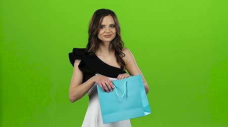 queda : Brunette girl holds a gift bag in her hands, she likes it. Green screen. Slow motion