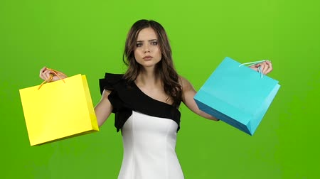 queda : Girl keeps the shopping bags and doubts what to choose. Green screen. Slow motion