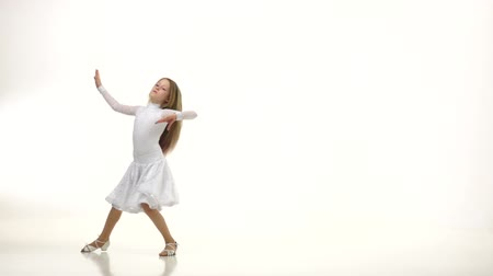 enduring : Child dances in a beautiful white dress on a parquet floor. White background. Slow monion