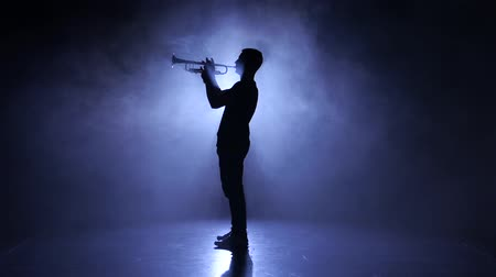 trombeta : Professional musician in smoky studio playing on wind instrument, silhouette Stock Footage