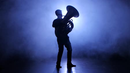 trombeta : Trumpeter man in spotlight in smoky studio plays on tuba