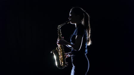 fife : Female musician playing on saxophone standing sideways on black studio Stock Footage