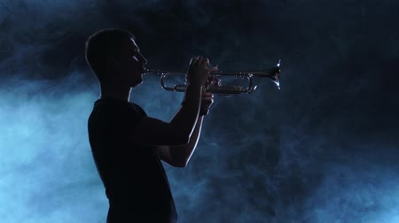 trombeta : Professional musician man playing on trumpet. Smoky silhouette, slow motion