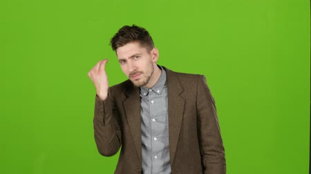 admires : Attractive male businessman adjusts his clothes, wipes his face, admires himself. Green screen