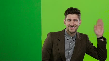 hides : Man looks out from behind the green board and waves. Green screen. Slow motion