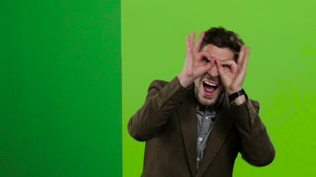 hides : Man looks out from behind the green board, makes grimaces, and hides. Green screen. Slow motion Stock Footage