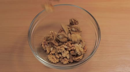 peeled grains : Core of walnuts are poured into glass dish. Slow motion Stock Footage