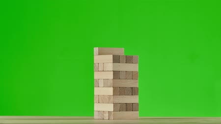 um objeto : Wooden puzzles gather in tall tower. Stop motion, green screen