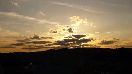 hides : Sky with clouds at sunset. Hilly with forests, time lapse