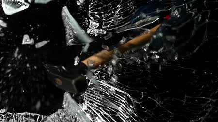shattering : Brings a hammer to the glass and hits it, it crumbles into small pieces. Black background. Slow motion