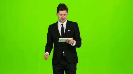 lépések : Businessman is going to work and prints important messages. Green screen