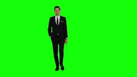 chroma key background : Guy walks down the street, puts his hand in his pocket and waves. Green screen