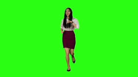 preocupações : Girl of Asian appearance with a phone is running to an important meeting. Green screen. Slow motion