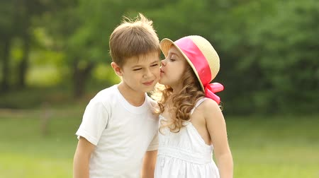 detém : Little girl kisses the boy on the cheek, he is embarrassed and smiles. Slow motion