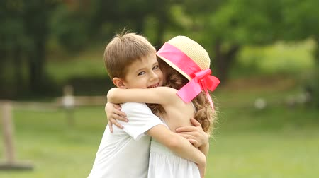 вокруг : Little boy is gently hugging the girl, they are happy and carefree. Slow motion Стоковые видеозаписи