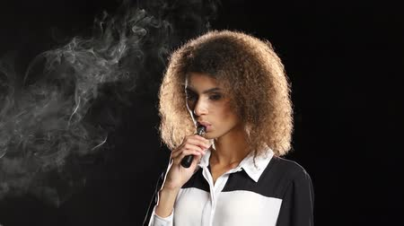 cygaro : African american girl smokes an e-cigarette in an empty room. Black background Wideo