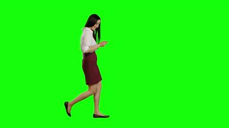 vzhled : Girl of asian appearance walks the street, the phone looks at interesting pictures. Green screen