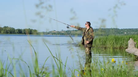 waders : Fisherman holds a fishing rod in his hand and catches fish for bait