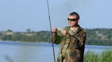waders : Man clings a bait to a fishing rod, he wants to catch fish