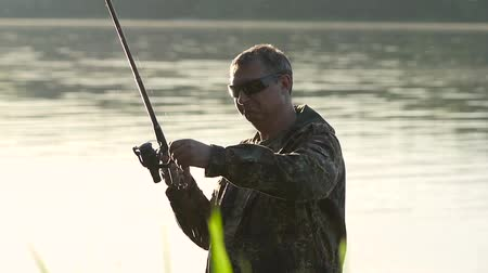 waders : Man clings a bait to a fishing rod, he wants to catch fish. Slow motion