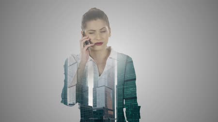 imposition : Business woman speaks by mobile phone double exposure over city skyline.