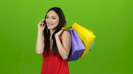 zsák : Girl is shopping with packages and talking on the phone. Green screen