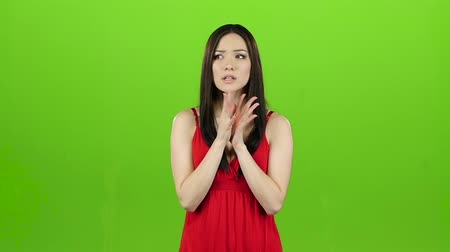 umma : Girl is asian, hoping for a win and crossing her fingers. Green screen. Slow motion