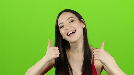 polegar : Girl s having fun and showing a thumbs up. Green screen. Slow motion